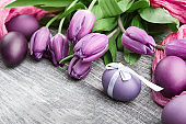 luxurious fresh fashionable purple tulips on a wooden background next to Easter eggs