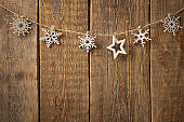Rope with snowflakes and star on wooden background