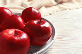 Plate with ripe red apples on wooden background