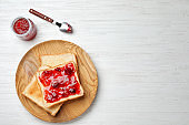 Toasts with jam on wooden background, top view