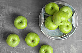 Composition with fresh green apples on grey table, top view