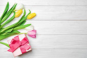 Tulips and gift box on wooden background, top view