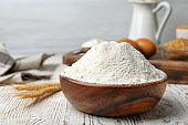 Bowl with flour on wooden table