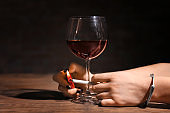 Woman in handcuffs lighting cigarette near glass of wine. Alcoholism and nicotine addiction