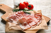 Board with raw bacon rashers on table
