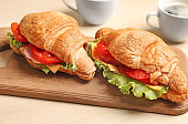 Wooden board with delicious croissant sandwiches on table