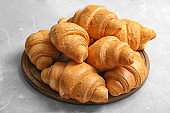 Wooden board with tasty croissants on table