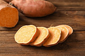 Slices of sweet potato on wooden background