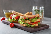 Wooden board with delicious sandwich on table, closeup