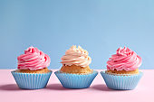 Yummy cupcakes on color background