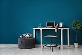 Comfortable home workplace with laptop on desk against color wall
