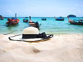 White straw hat on white sand beach.