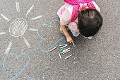 Top view image of happy little girl wears pink dress and backpack drawing with colorful chalks on the sidewalk. Cute child preschooler play outdoor on pavement. Toddler educational activity outside.