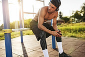 Athlete muscular young male relaxing after training on workout ground outdoors. Handsome shirtless sportsman looking away with smart phone in hands with headphone listening music posing on sunlight
