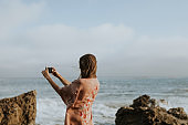Blonde woman using smartphone taking a photos by the sea