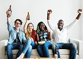 Group of diverse friends drinking and cheering while watching sports together