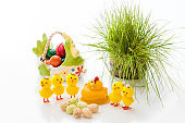 Yellow Easter Chicks and basket ceramic Easter eggs on a light background. Copy space