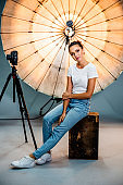 Model posing in front of a reflective umbrella in a studio