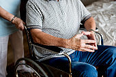 A man on a wheelchair with and assistance
