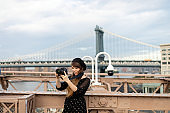 Photographer taking a photo at the Brooklyn Bridge, USA