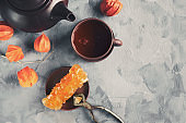 Brown Grape sugar in clear crystals, tea and tongs on grey slate close-up. Oriental sweetness to tea. Copy spase