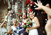 Family throwing rose petals at the newly wed bride and groom