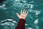 Female hand overlooking the blue water