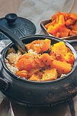 Combined porridge of wheat and rice with large pieces of baked ripe pumpkin in a beautiful ceramic bowl. Rustic