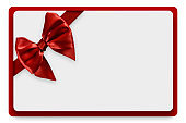 Greeting card with red satin ribbon and bow, isolated on white background