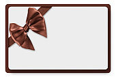 Greeting card with brown-chocolate satin ribbon and bow, isolated on white background