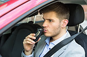 Man Sitting Inside Car Taking Alcohol Test