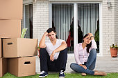 Upset Couple Sitting Near Stacked Cardboard Boxes