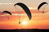 Silhouette Of Paragliders At Sunset