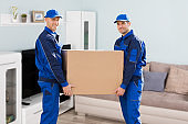 Two Delivery Man Holding Cardboard Box