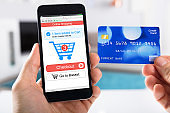 Person Using Credit Card For Shopping Online On Smartphone