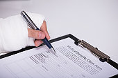 Person With Fractured Hand Filling Medical Benefit Claim Form