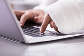 Man With Wrapped Bandage On His Hand Using Laptop