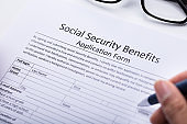 Person Filling Social Security Benefits Application Form