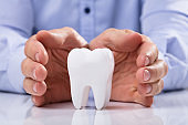 Man's Hand Protecting White Tooth