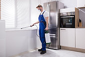 Exterminator Worker Spraying Insecticide Chemical