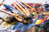 Close-up Of Various Messy Paintbrushes