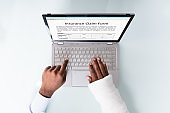 Businessman With Bandage Hand Filling Insurance Claim Form