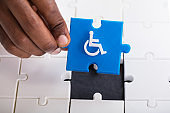 Hand Holding Disabled Wheelchair Icon On Jigsaw Puzzle