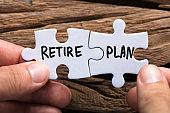Hands Holding Retire Plan Matching Jigsaw Pieces