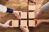 Businesspeople Arranging The Wooden Block
