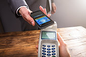 Businessperson Paying With Smartphone Using NFC Technology