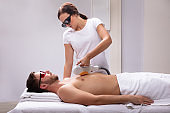 Beautician Giving Laser Depilation Treatment On Man's Chest