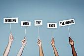 Hands hold aloft sign' winning with the best teamwork'
