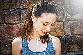 Beautiful girl wearing in-ear headphones looks down, smiling