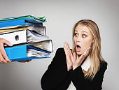 Young blonde businesswoman is alarmed by huge pile of files